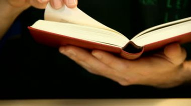 stock-footage-reading-a-book-holding-it-in-hand-flipping-a-page-shot-on-slider